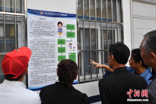 资料图:民众阅读办理居住证的相关要求细则。 中新社记者 崔楠 摄