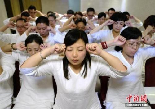 """资料图:长沙首个睡眠班开课,学员们身穿白色睡衣做睡眠操。这些学员均为""""白领""""阶层,优质的睡眠或有助于缓解他们平日的工作压力。中新社发 杨华峰 摄"""