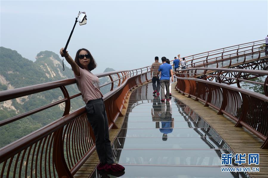 7月15日,游客在少华山玻璃栈道自拍留影。