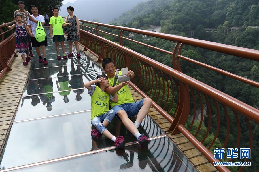7月15日,游客在少华山玻璃栈道合影留念。