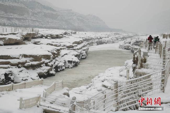 陕西多地迎来2018年的首场降雪。延安黄河壶口瀑布一片银装素裹,瀑布两岸被积雪覆盖,岩石和护栏上出现大小不一、形态各异的冰挂,积雪和冰挂让冬日里的壶口瀑布更显辽阔与壮观。梁鹏 摄