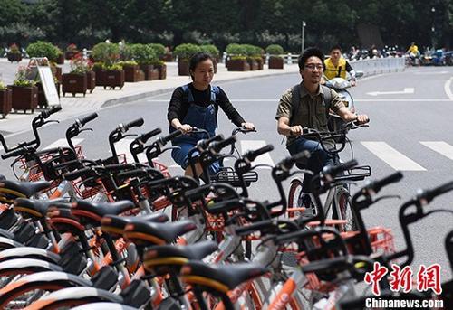 资料图:两名市民正在从摆放的共享单车前骑过。 <a target='_blank' href='http://www.chinanews.com/'>中新社</a>记者 王刚 摄