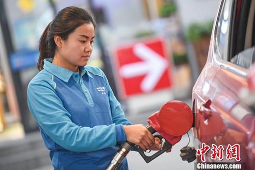 9月30日,山西太原,加油站工作人员给汽车加油。当日,国家发改委下发通知,自9月30日24时起,国内汽油价格每吨上调240元,柴油价格每吨上调230元。<a target='_blank' href='http://www.chinanews.com/'>中新社</a>记者 武俊杰 摄