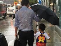 """父亲全身湿透""""为儿撑伞"""""""