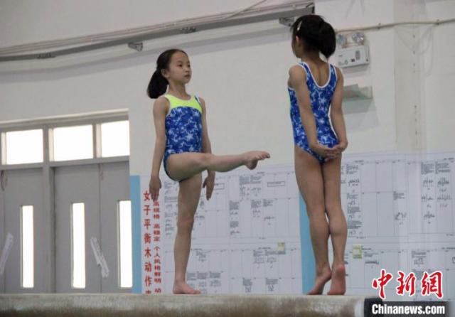 图为在陕西省体育训练中心的体操馆,高低杠、鞍马、平衡木等项目的运动员在教练员的辅助下对技术动作进行反复练习。 张一辰 摄