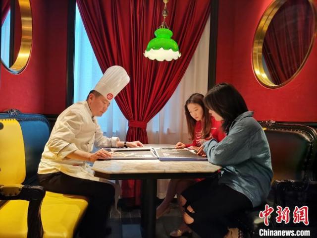 """5月24日,记者在济南一鲁菜馆见到网络主播李頔时,她正在餐馆中向厨师了解当天所要进行""""吃播""""的鲁菜菜式、文化及用料选材方面的讲究。 郝学娟 摄"""